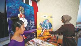 A Palestinian artist, Abeer Jibril, works on ballet paintings as her daughter Maya looks at her at t