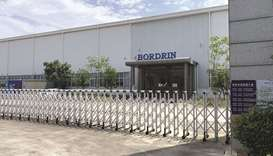 Bordrin's factory in Nanjing. Weeds dot the factory's perimeter and there's a court notice pasted to