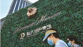 People walk past a residential building developed by Evergrande in Pudong district in Shanghai on Se