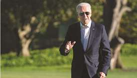US President Joe Biden walks across the South Lawn of the White House after arriving aboard Marine O