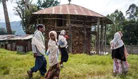 Ethiopian Orthodox devotees walk outside a church in Anderacha, formerly the site of a palace of the