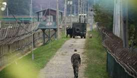 A South Korean soldier walks along a military fence near the demilitarized zone separating the two K