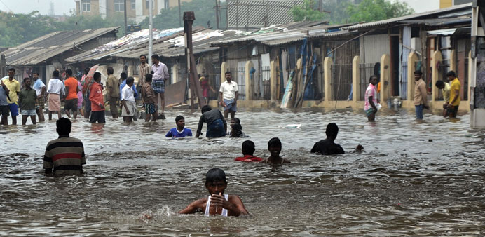 Locals wade through a waterlogged street in Chennai yesterday.