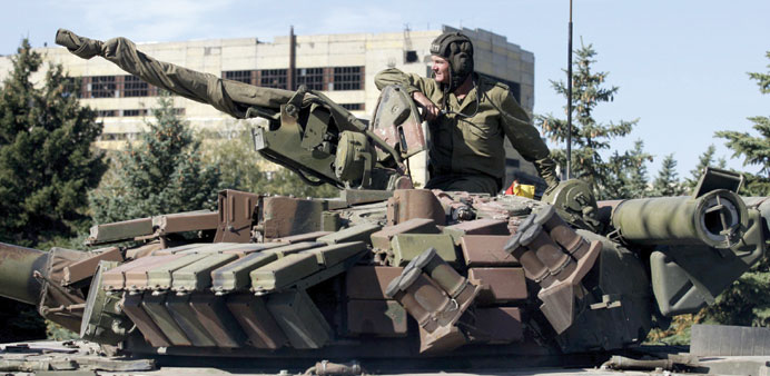 A member of the self-proclaimed Luhansk People's Republic forces sits on a tank outside Luhansk, Ukr