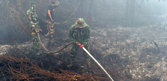 Indonesian soldiers along with firemen put out a fire on a farm land in Kampar, Riau Province yester