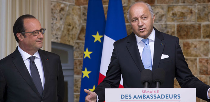 French Foreign Affairs Minister Laurent Fabius (R) delivers a speech next to French President FranCo