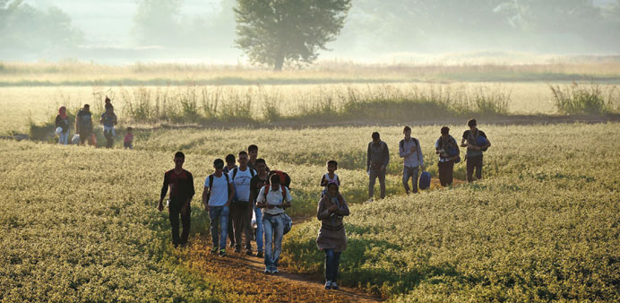 Migrants walking through a field to cross the border from Greece to Macedonia near the Greek village
