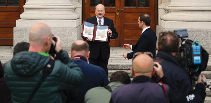 Irish Finance Minister, Michael Noonan poses with a copy of the 2016 budget during a photocall in fr