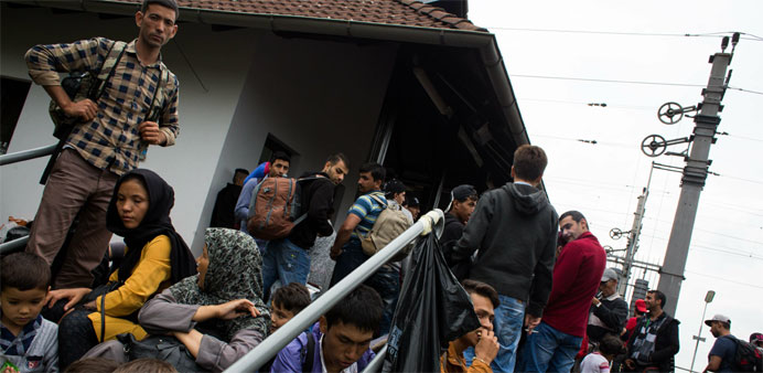 Migrants wait to board a train to Vienna at the railway station in Nickelsdorf