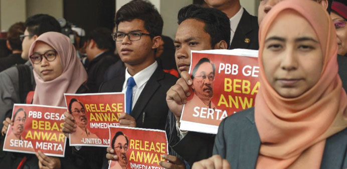 Members of Malaysian opposition hold placards reading 'Release Anwar immediately!', after a press co