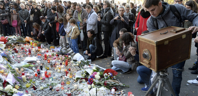 People gather in front of a memorial along a police cordon set-up close to the Bataclan concert hall