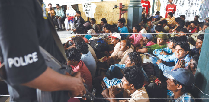 Released Indian fishermen prisoners wait at the railway station in Karachi yesterday.