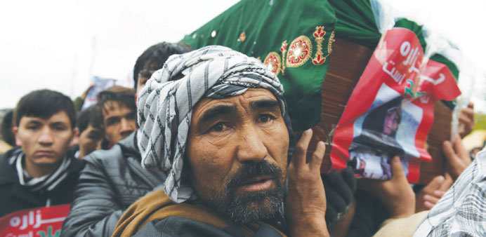 Afghan protesters carry a coffin containing a decapitated body of one of seven Shia Hazaras, includi