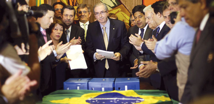 President of Brazil's chamber of deputies, Eduardo Cunha (centre), receives a new petition to Congre