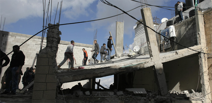 Palestinians check the house of a man who carried out a car-ramming attack last year, after it was d