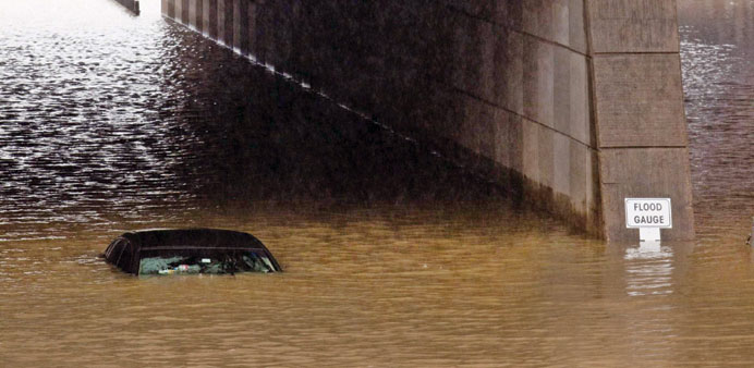 A Uber driver talks on the phone after he drove his car into high water in Houston, Texas, yesterday