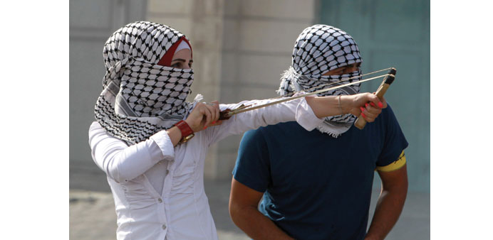 A young Palestinian woman uses a slingshot during clashes with Israeli security forces yesterday in