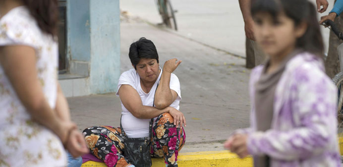 A woman sits on the sidewalk after a tremor in El Galpon, northwest Argentina.