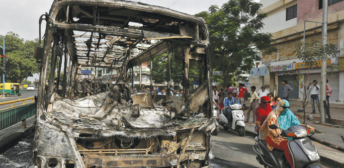 Commuters ride past the wreckage of a bus burnt in the clashes between the police and protesters in