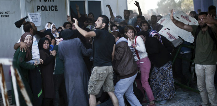 Migrants try to protect themselves from stones as Afghans and Syrian migrants scuffle over priority