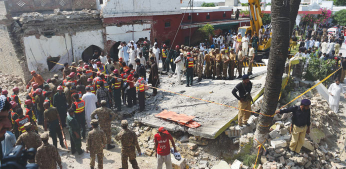 Pakistani army and rescue officials gather around a collapsed building at a suicide bomb blast site