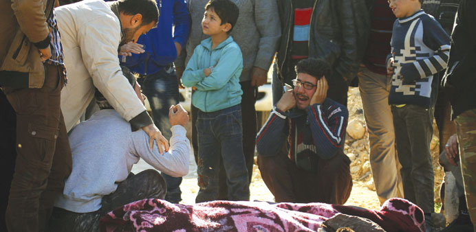 People mourn over bodies of people killed in air strikes believed to have been carried out by the Ru