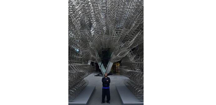 "Ai Weiwei poses in front of his sculpture ""Forever"" at the base of the ""Gherkin"" tower in the City o"