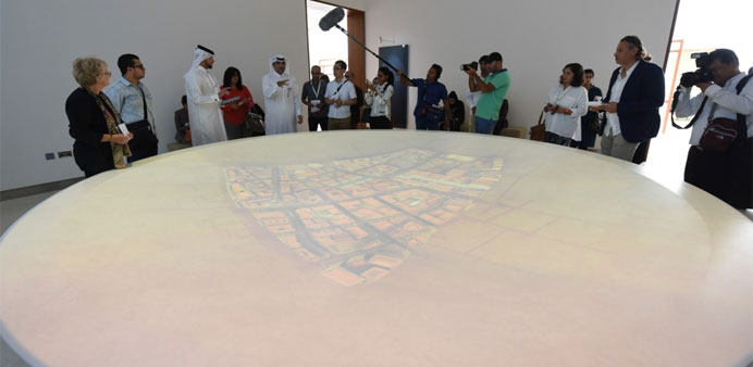Ali shows to journalists how the interactive media dish at Mohamed Bin Jassim House works.
