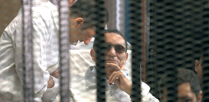 Gamal Mubarak (left) and brother Alaa with their father Hosni Mubarak in a cage inside the courtroom