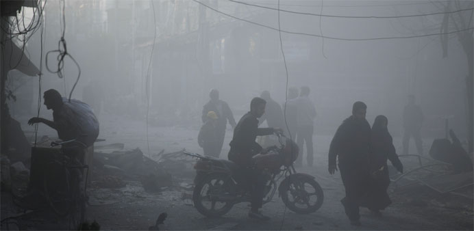Syrians walk in a dusty street as the sound of fighter jets can be heard overhead following air stri