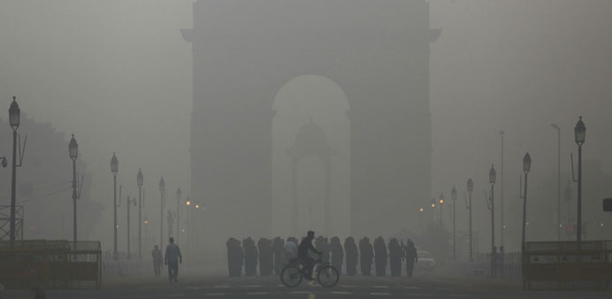 A man rides his bicycle next to soldiers marching in front of India Gate on a smoggy morning in New