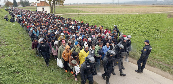 About 1,000 migrants are escorted by Slovenian police officers from the border crossing with Croatia