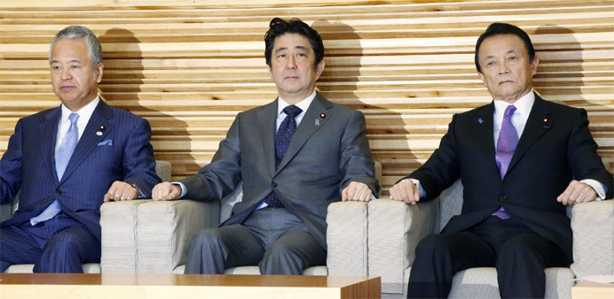 Japan's Prime Minister Shinzo Abe (C), accompanied by Finance Minister Taro Aso (R) and Economic Rev