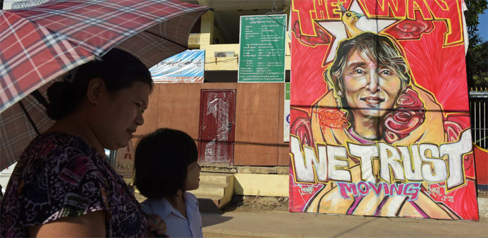 People walk past a graffiti depiction of Myanmar's Aung San Suu Kyi