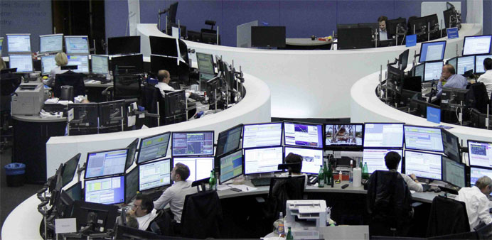 Traders are pictured at their desks in front of the DAX board at the stock exchange