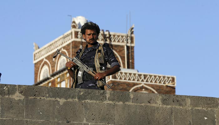 A Houthi militant stands guard on a bridge in Sanaa.