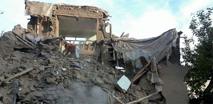An Afghan man digs through the rubble of a damaged building after a powerful earthquake in Ramankhee
