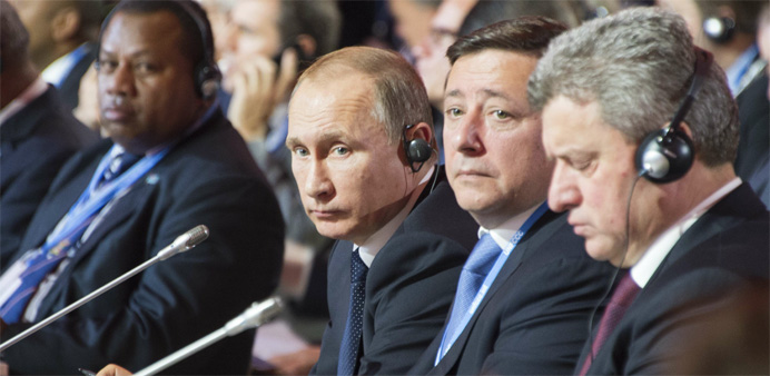 Russian President Vladimir Putin (C) listens as US President addresses opening ceremony of the World