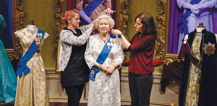 Stylists Jane Anderson (left) and Luisa Compabassi pose with the re-styled wax figure of Queen Eliza