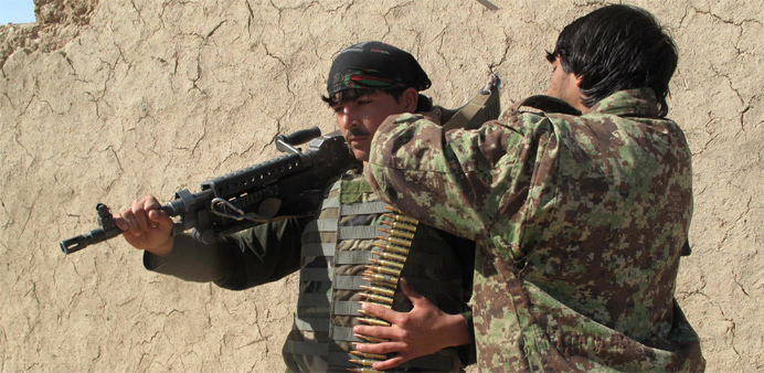 Afghan National Army (ANA) soldiers adjust their equipment in Helmand