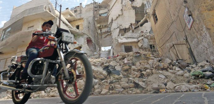 A boy rides a motorcycle through a street in Old Aleppo yesterday.