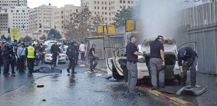 Israeli policemen inspect the car of a Palestinian, whose body lies on the ground, after he was shot