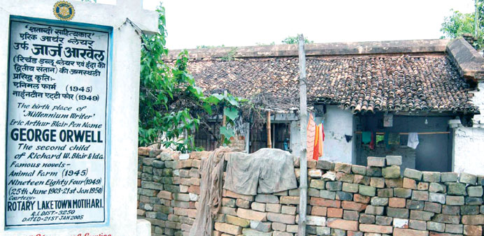 A signpost announces the birthplace of George Orwell in front of a dilapidated residence in Motihari