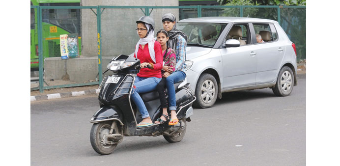 A helmeted woman rides her moped carrying two friends without helmets in New Delhi yesterday.