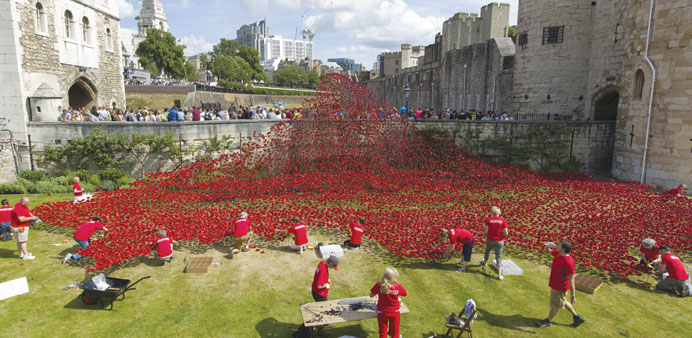 Volunteers install porcelain poppies as part of the art installation 'Blood Swept Lands and Seas of