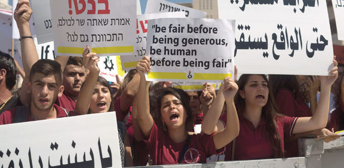 Arab Israeli Christian students hold placards during the protest in Jerusalem yesterday.