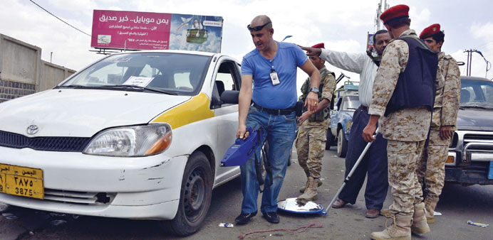 An expert uses an explosives detector as he checks vehicles at a checkpoint amid fears of Al Qaeda c