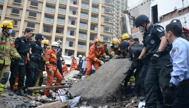 Rescue workers search at the site where residential buildings collapsed in Wenzhou, Zhejiang provinc