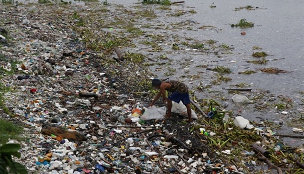 A resident collects recyclable materials from debris along the shore in Manila bay after Typhoon Sar