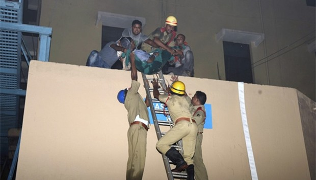 Indian rescue workers lowering a victim of the massive fire at SUM hospital building